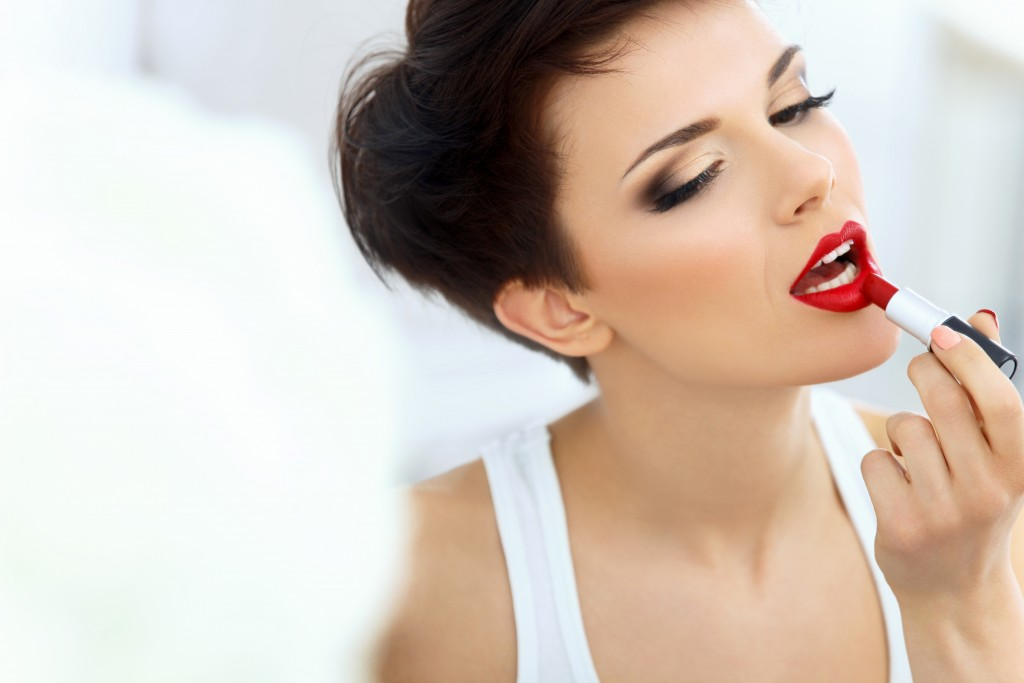 Beautiful Brunette applies lipstick. Lipgloss and Brush. Red lips Makeup